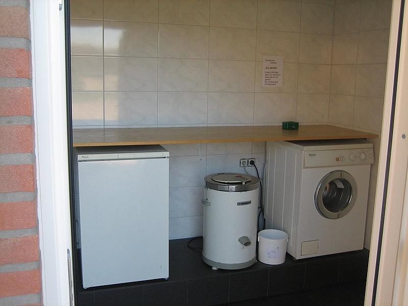 Wasruimte met wasmachine en drogers